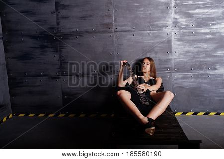 Portrait Of Sexy Brunette Girl At Black Underwear With Guitar Sitting Wooden Lounger At Industrial B
