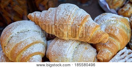 Tasty croissants with spikelets on colour background