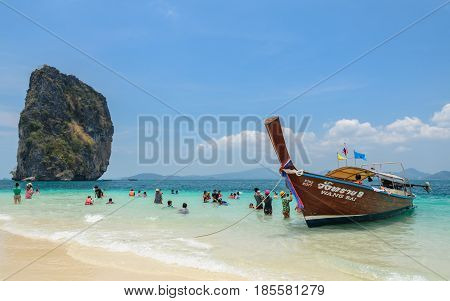 KRABI THAILAND - APRIL 12 2016 : Poda Island white sandy beach with turquoise andaman sea water and long-tailed boat taxi in Krabi province, Thailand.