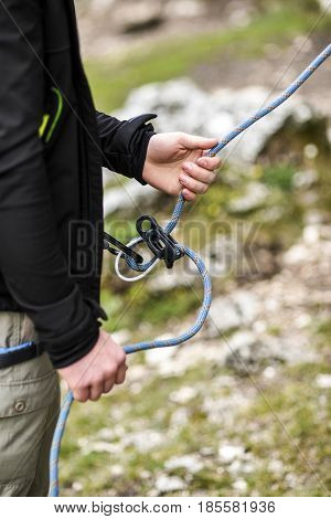 Climbing belayer holding rope in his hands.