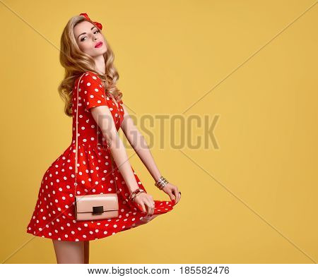 PinUp Sensual Blond Girl Having fun.Fashion Woman Smiling in Red Polka Dots Summer Dress. Stylish Curly hairstyle, Trendy Clutch, Makeup, Bow. Glamour Playful Sexy Beauty pinup Model.Vintage on Yellow