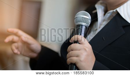 blurred of Businesswoman speech with microphone hand gesturing protesting or belief concept for explaining