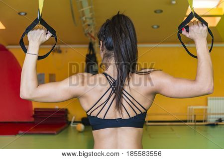 Strong young woman doing suspension training in the gym