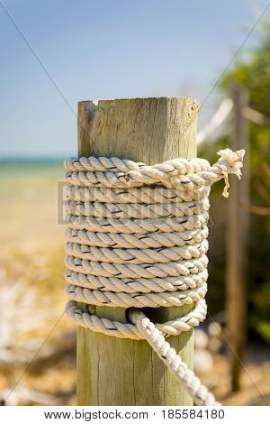 Marine rope tied to a wooden pole beside the ocean