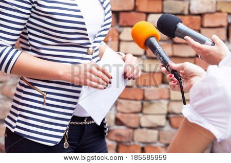 Reporters holding microphones interviewing woman. Press interview. News conference. Journalism.