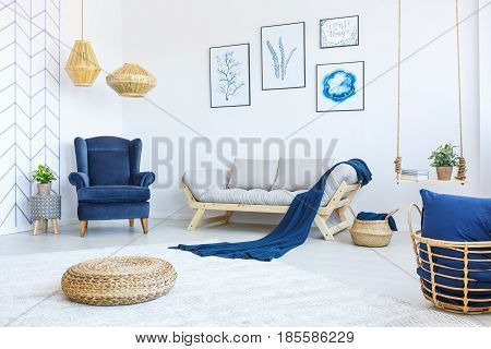 New white living room with blue armchair sofa rattan pouf