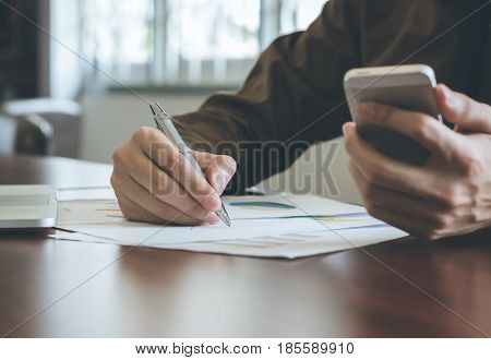 Businessman analyzing graph document with laptop and using cell phone.