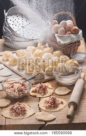 The dumplings made for cooking, floured and dough with forcemeat on a table-top from an oak in style a rustic