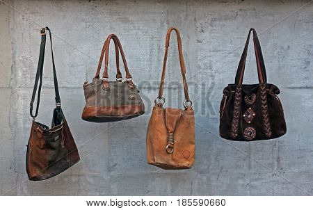 Old brown female leather handbags on grey background
