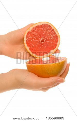 Two pieces of grapefruit with one white capsules isolated on white