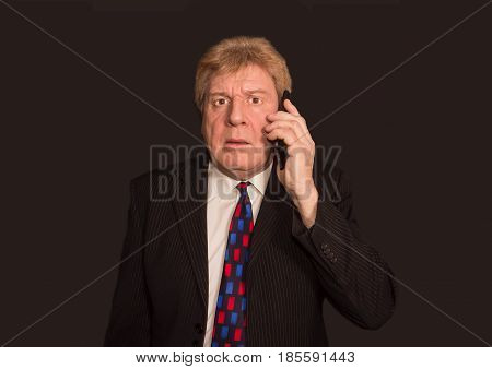 Shocking news. Surprised and sad man in formalwear holding mobile phone and standing against black studio background