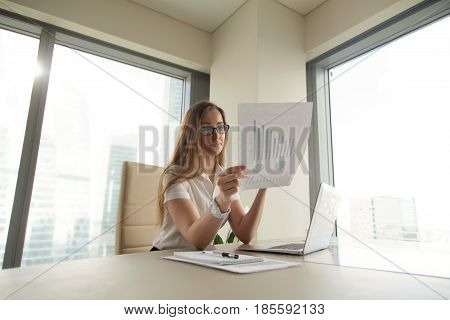 Businesswoman sitting at the desk with laptop and reading document with financial graphs, charts, diagrams. Female trader analyzing fluctuations on stock market. Entrepreneur looking statistics data