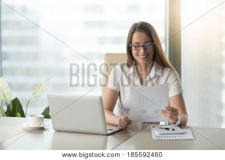 Smiling businesswoman revising company financial results. Happy woman reading document with graphs, diagrams stats at workplace. Female office worker satisfied with market analysis, financial forecast