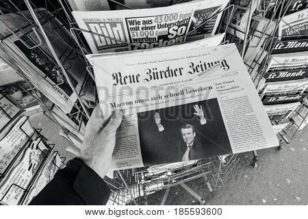PARIS FRANCE - MAY 9 2017: Pov buying Neue Burcher Zeitung newspaper front page with the picture of the newly elected French president Emmanuel Macron after the second round French Presidential election
