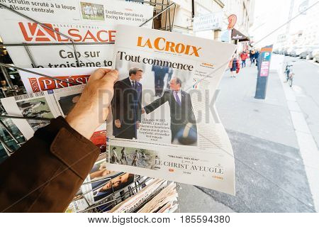 PARIS FRANCE - MAY 9 2017: Pov buying La Croix newspaper front page picture of the newly elected French president Emmanuel Macron next to Francois Hollande after second round French Presidential election