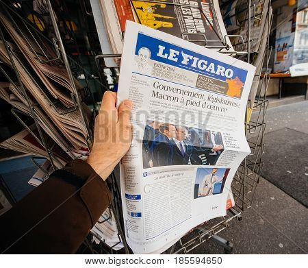 PARIS FRANCE - MAY 9 2017: Pov buying Le Figaro newspaper front page with the picture of the newly elected French president Emmanuel Macron after the second round French Presidential election