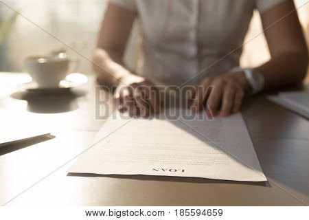 Woman sitting at the desk with loan agreement form. Close up photo of female hands lying on business document. Businesswoman reading  contract terms. Financial adviser analyzing lending conditions