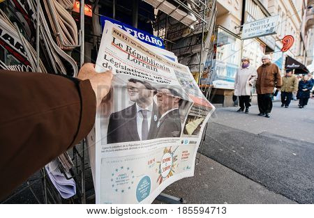 PARIS FRANCE - MAY 9 2017: Pov buying le republicain lorrain newspaper front page with the picture of the newly elected French president Emmanuel Macron after the second round French Presidential election