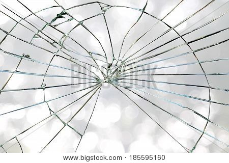 Broken window glass on a grayish bright bokeh background