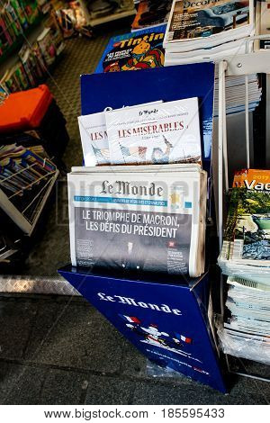 PARIS FRANCE - MAY 9 2017: Pov buying Le Monde with President's Challenges title newspaper front page with the picture of the newly elected French president Emmanuel Macron after the second round French Presidential election