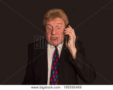 Shocking news. Surprised and angry senior man in formalwear holding mobile phone and standing against black studio background