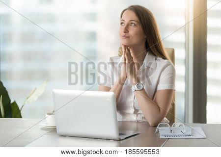 Dreamy businesswoman anticipates dearest wish comes true. Happy young woman with exited facial expression imagines her great success while sitting at office. Female seeing herself in incredible future