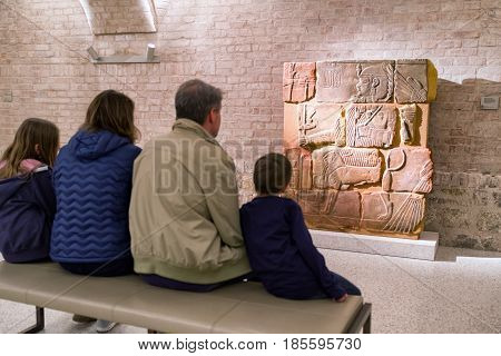 BERLIN GERMANY - APRIL 7: Family watching on egyptian paintings on the wall in Egyptian museum on April 7 2017 in Berlin