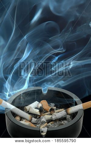 Burning cigarettes left in an ashtray with a lot of smoke in a stuffy room