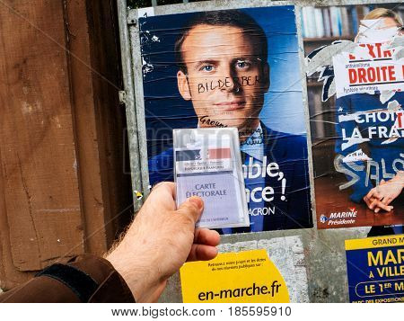 PARIS FRANCE - MAY 9 2017: Carte Electorale in front of Emmanuel Macron portrait poster detail next to polling place after the second round of the French presidential election with the marker inscription Member of Bilderberg group