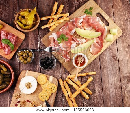 Italian antipasti wine snacks set. Cheese variety Mediterranean olives pickles Prosciutto di Parma with melon salami and wine in glasses over black grunge background