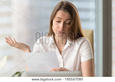 Businesswoman upset because of low financial results. Sad female entrepreneur reading document with bad statistics. Skeptical woman examines confusingbusiness report letter. Forecast falling of profit