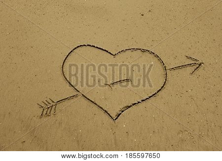 Heart with an arrow through it drawn in the sand