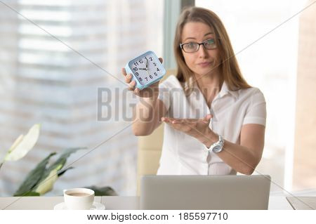 Woman at the desk pointing on clock. Female entrepreneur motivates colleagues hurry to finish job in time. Businesswoman scolding an employee for being late. Punctuality and compliance deadlines