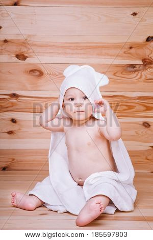 Baby Boy With Brown Eyes Is Five Months Old Wrapped In A White Towel With Ears On Wooden Background