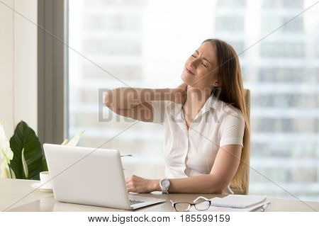 Businesswoman feeling pain in neck after sitting at the table with laptop. Tired female suffering of office syndrome because of long hours computer work. Pretty girl massaging her tense neck muscles