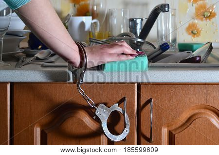 Female Hand With Sponge, Handcuffed To A Kitchen Counter With A Lot Of Unwashed Dishes