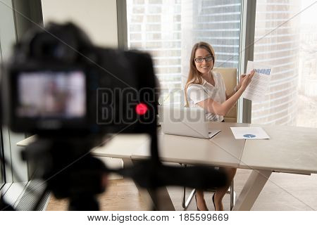 Attractive woman sitting at desk with laptop and showing document with stats on camera. Female entrepreneur recording business vlog. Video presentation for social networks, blog or company web page