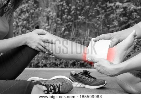 Young woman runner ankle being applied bandage by man in park. injury ankle - black and white concept