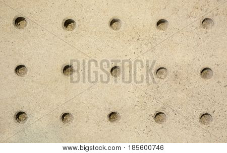 Stone wall patterned with round holes texture background, yellow grainy surface