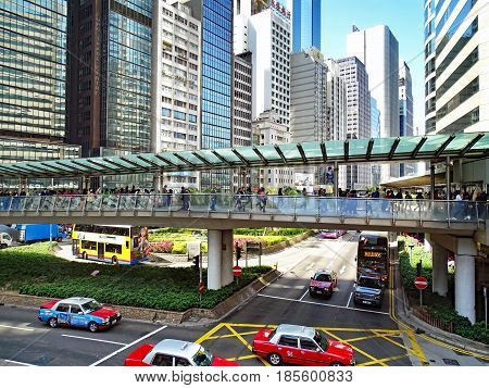 Central, Hong Kong - February 09, 2016: Traffic between high-rise buildings during the rush hour in the Central District on Hong Kong Island. Many people walk on a pedestrian bridge over a road crossing which is driven by cars and buses.