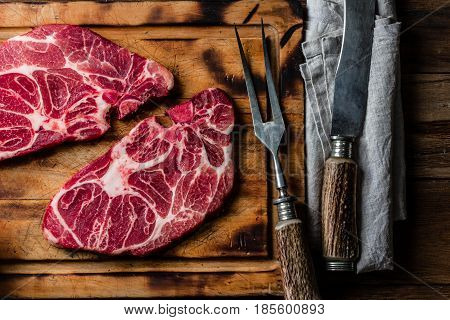 Meat. Two raw beef marbled meat steak on wooden cutting board, meat carving set, rustic background. Top view