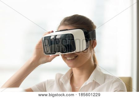 Smiling young woman looking in virtual reality glasses. Female enjoying VR technology digital simulation. Girl entertains with electronics 3d goggles. Virtually conversation with colleagues or friends