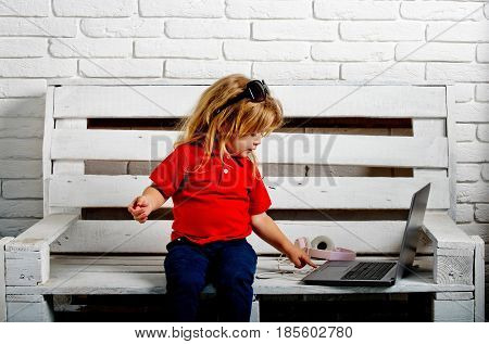 Child Or Small Boy With Laptop And Headphones