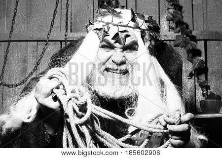 Zeus god man or jupiter with rope and vine crown on long hair with beard black and white