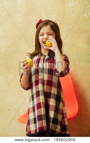 Cute small little girl child with winking eyes eating yellow fresh vitamin lemons citrus fruit with sour taste at orange plastic chair on beige wall. Healthy food and vegetarian diet