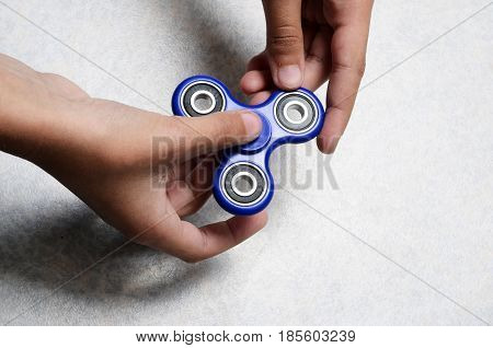 Blue Hand spinner fidgeting hand toy in child's hands