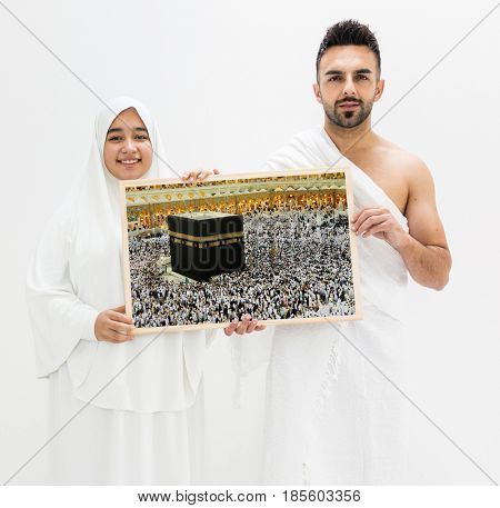 Muslim man posing as ready for Hajj visiting Kaaba in Mecca holding banner frame of The Holy Place