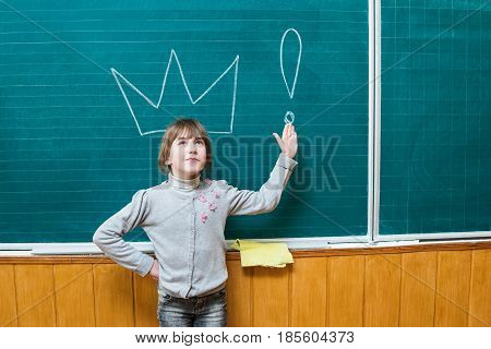 Schoolgirl stands at the school board and points to the crown drawn on it and an exclamation mark