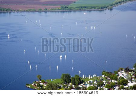 View of Nove Mlyny - Musov lake with boats sailing boats and windsurfing in the rain in Palava - South Moravia