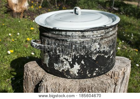 Old used grunge enameled metal saucepot blackened by fire on wooden stump in farmyard in sunny springtime day